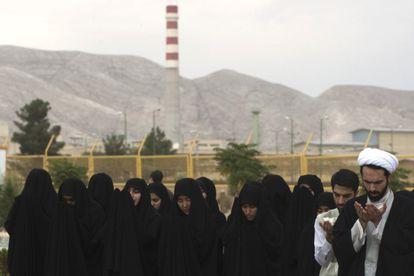 Varias mujeres y clérigos rezan junto a las instalaciones nucleares de Isfahan.