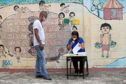 Un hombre acude a buscar libros y material escolar en la escuela Eulalio Arias, durante el inicio oficial del año escolar 2020, en Santo Domingo.