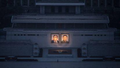 Un ciudadano pasea debajo de los dos grandes retratos de Kim Il-Sung (izq.) y Kim Jong-Il (der.) en Pyongyang.