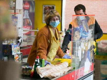 Una cajera atiende a un cliente en un supermercado en Manzanares el Real (Madrid).