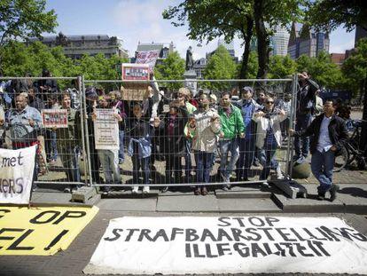 Decenas de refugiados gritan eslóganes contra la criminalización de los inmigrantes ilegales, el miércoles en La Haya.