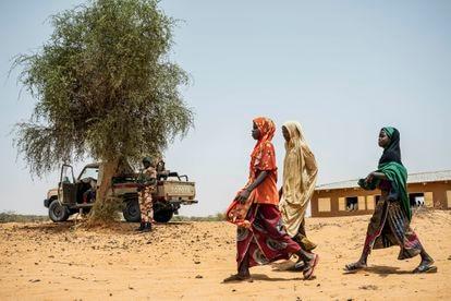 Tres niñas pasan junto a una patrulla de la Guardia Nacional de Níger en el pueblo de Inizdan, en el norte de Tillabéri, escenario de frecuentes ataques yihadistas.