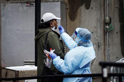 A un paciente se le realiza una prueba COVID-19 por un trabajador médico fuera del Brooklyn Hospital Center, el domingo 29 de marzo de 2020, en el distrito de Brooklyn de Nueva York.