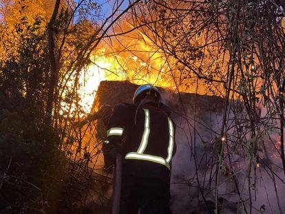 Los bomberos intentan apagar el incendio originado el sábado junto al pantano de San Juan, el pasado agosto.