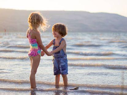 Dos niños juegan en la orilla del mar.