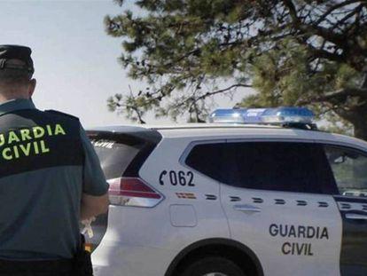 Un guardia civil delante de un coche patrulla, en una imagen de archivo.