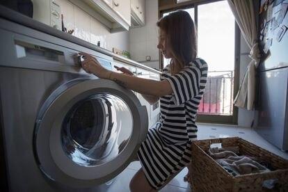 Mujer pone una lavadora en su domicilio en Madrid, el 8 de marzo de 2021.