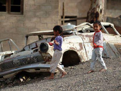 Niños juegan cerca de un coche en Saná, la capital de Yemen