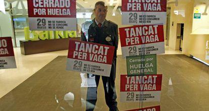 Un guarda de seguridad protege la entrada de la oficina de la sede de Bancaja en Valencia.