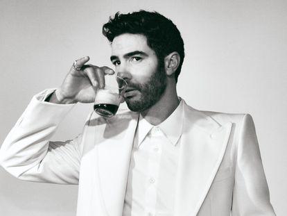 El actor francés viste traje claro con solapa ancha y camisa blanca, todo, Louis Vuitton.