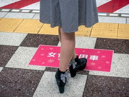 Una mujer espera en un andén del metro de Tokio.