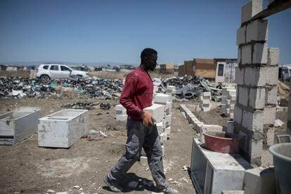 Madou ayuda a su amigo Mamadou a construir su casa.