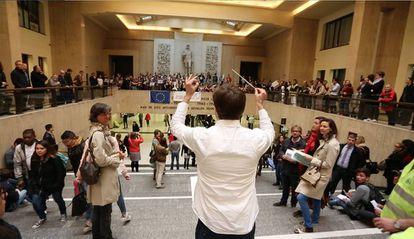 Músicos interpretan el 'Himno de la alegría' en la Estación Central de Bruselas en señal de protesta por el fin de la orquesta.