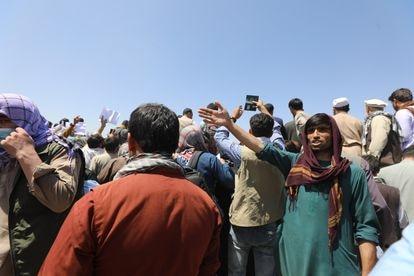 Algunos afganos muestran sus pasaportes para lograr superar los controles.