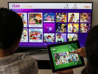 Dos niños eligen programas en una Smart TV y una tableta.