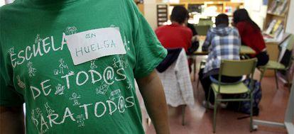 Un profesor del instituto Ignacio Ellacuría de Alcorcón (Madrid) luce una camiseta en favor de la escuela pública y un cartel anunciando la huelga en la biblioteca del centro