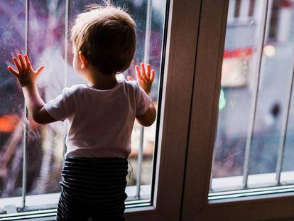 Un niño mira por la ventana de su cuarto la calle.