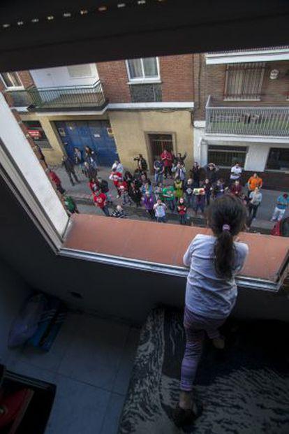 Una niña mira desde la ventana a un grupo de manifestantes que protesta contra el desahucio de su familia