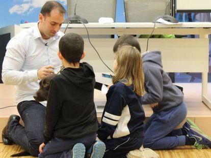 Unos niños acarician a 'Kiwi' en presencia de su adiestrador.
