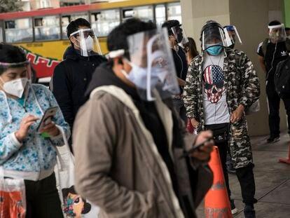 Algunas personas a las afueras de una estación de tren en Lima, el pasado 25 de julio.