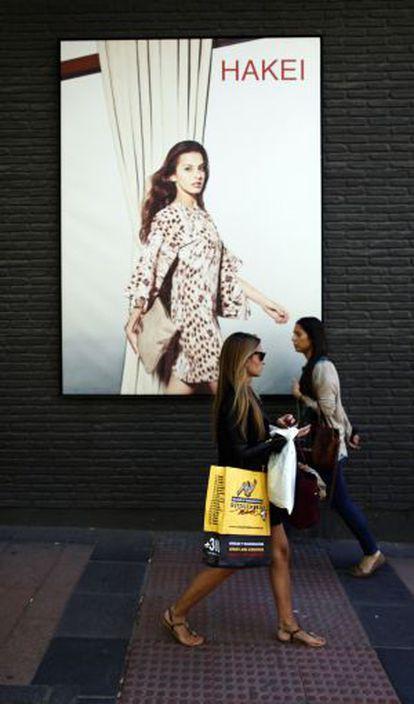 Una mujer pasea con bolsas en la calle de Serrano.