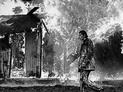 Un hombre camina ante un edificio ardiendo durante los 'Troubles' (National Library of Ireland).