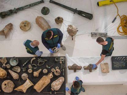 Agentes de la Guardia Civil revisan objetos arqueológicos expoliados.