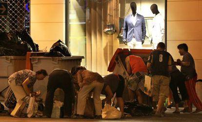 Un grupo de personas buscan en bolsas de basura alimentos a las puertas de un centro comercial en la calle Alberto Aguilera, en Madrid, en una imagen de archivo.