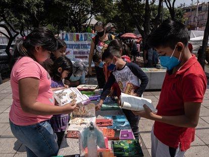 Varios niños revisan la colección '21 para el 21' en un tianguis de Coyoacán, el 2 de octubre.