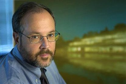 Gerald M. Rubin, director de Janelia, posa con una imagen del centro de investigación a la derecha.