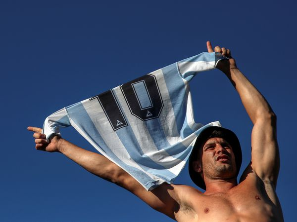 A man holds a Maradona's t-shirt as he stands on the fence of the Casa Rosada presidential palace, where people gather to mourn the death of soccer legend Diego Armando Maradona, in Buenos Aires, Argentina, November 26, 2020. REUTERS/Ricardo Moraes
