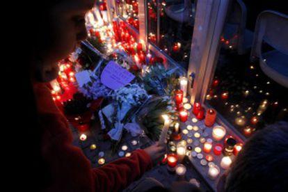 Varias personas depositan flores y velas a las puertas del Instituto Joan Fuster.