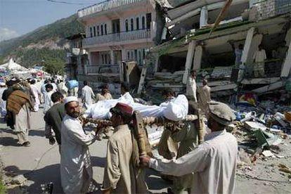 Varios habitantes de Balakot (Pakistán) portaban ayer un cadáver junto a un edificio derruido.