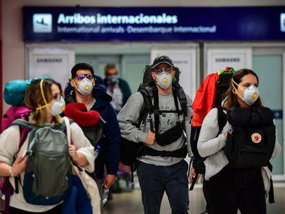 Pasajeros con mascarillas a su llegada al aeropuerto internacional de Ezeiza, en Buenos Aires
