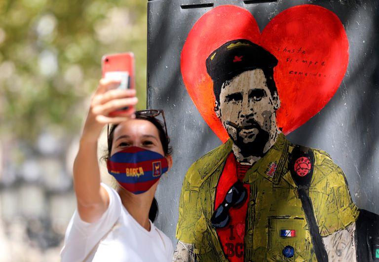 Una mujer se toma una fotografía con el grafiti de Messi vestido como el Che Guevara.