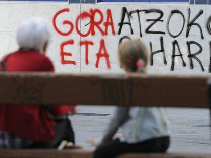 Una anciana y una niña sentadas en una calle de Vitoria, ante una pintada en favor de ETA en marzo de 2017.