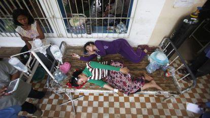 Dos trabajadoras camboyanas heridas descansan en el hospital tras el desplome de una planta de la empresa textil en la que trabajan.