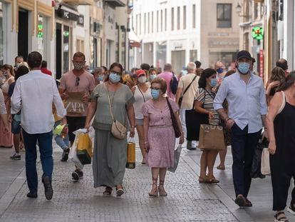 Varias personas con mascarilla por las calles comerciales del centro de Sevilla.