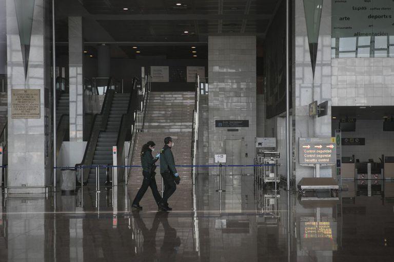 Dos trabajadores recorren la Terminal 2 del aeropuerto de El Prat una vez cerrada tras la cancelación masiva de vuelos.