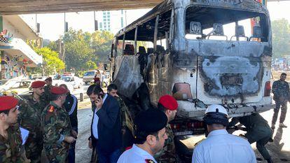 Miembros del Ejército sirio observan un autobús atacado con artefactos explosivos en Damasco, Siria, este miércoles.
