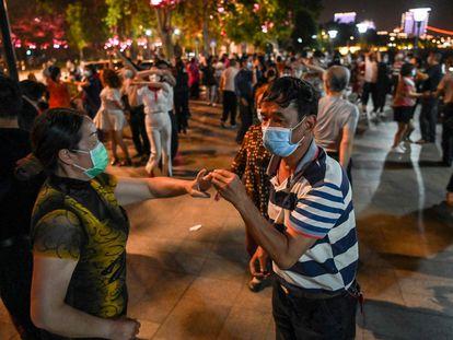 Parejas con mascarillas bailan en un parque junto al río Yangtzé, en Wuhan.