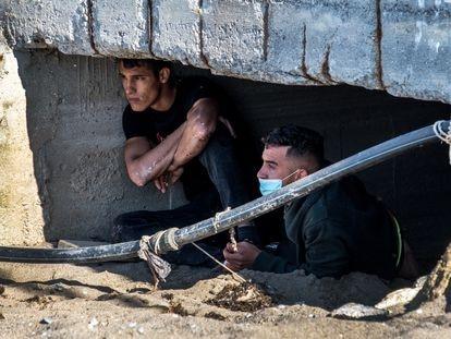 Dos chicos marroquíes se esconden de la policía en la playa Benítez, en Ceuta, para evitar su expulsión.