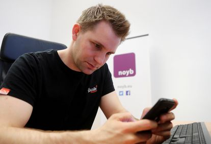 Schrems checks his cell phone at his Vienna office.