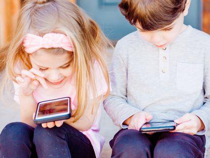 Dos niños juegan con el móvil.