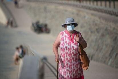 Una mujer con mascarilla camina por el paseo de la playa del Bogatell.