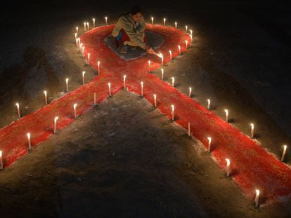 An Indian sex worker lights candles forming the shape of a ribbon as part of an awareness event on the occasion of World AIDS Day in Siliguri on December 1, 2018. - World AIDS Day has been observed today since 1988 to raise awareness of the AIDS pandemic. (Photo by DIPTENDU DUTTA / AFP)