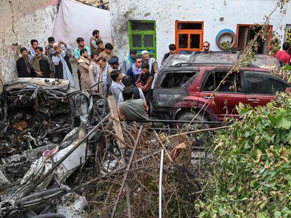 Vecinos y familiares de las víctimas junto al vehículo bombardeado por un dron estadounidense en Kabul el domingo.