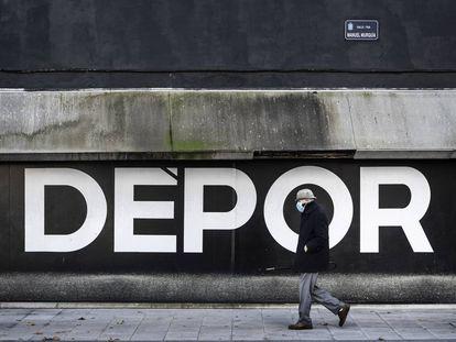 Un hombre camina junto a la fachada del estadio de Riazor, en A Coruña.