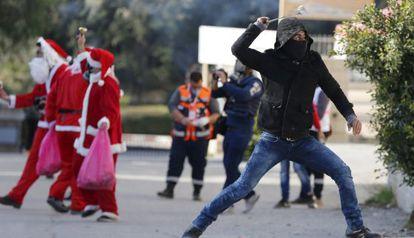 Un palestino lanza una piedra con una honda a soldados israelíes, con varios hombres vestidos de Santa Claus a su espalda, en Belén.