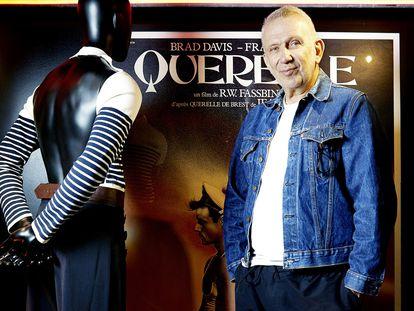 Gaultier posa junto al cartel de Querelle y uno de sus diseños inspirados en el filme.